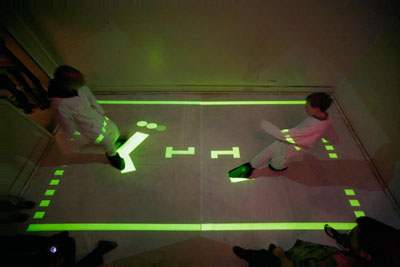 players playing pong, with their feet, on projected board
